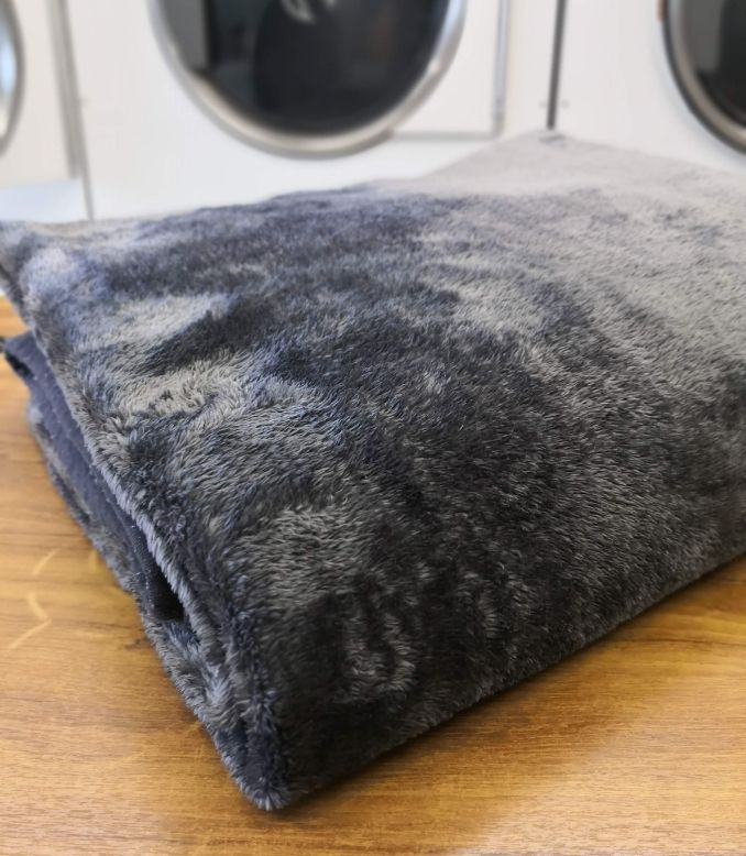 Folded clean mink blanket on folding table in laundry